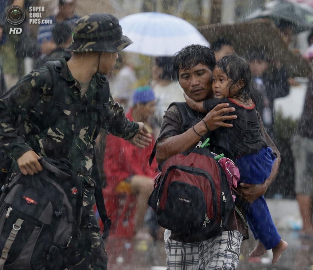 Филиппины. Таклобан. 12 ноября. Мужчина с дочерью спешат на борт самолета. (AP Photo/Bullit Marquez)