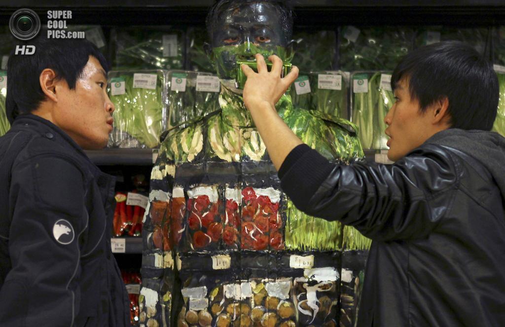 Китай. Пекин. 10 ноября 2011 года. Ассистенты показывают Лю Болиню результаты постановки. (REUTERS/China Daily)