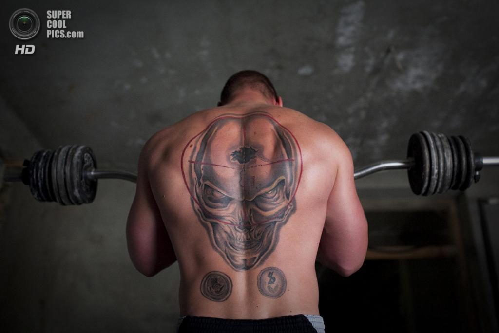 Афганистан. Чар-Дарах, Кундуз. 17 сентября 2011 года. Немецкий солдат с эффектной татуировкой на всю спину во время силовых упражнений на боевом посту. (AP Photo/Anja Niedringhaus)