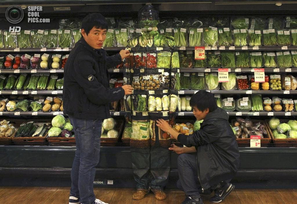 Китай. Пекин. 10 ноября 2011 года. Складки одежды недостаточно хорошо сливаются с фоном, приходится поправлять. (REUTERS/China Daily)