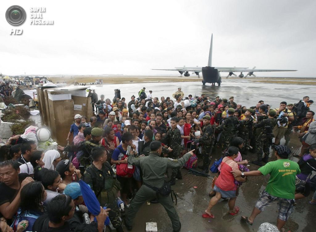 Филиппины. Таклобан. 12 ноября. Люди пытаются прорваться к самолету. (AP Photo/Bullit Marquez)