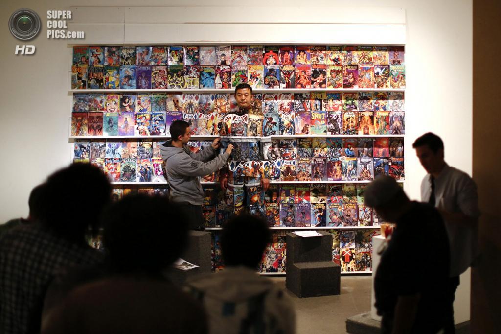 Венесуэла. Каракас. 2 ноября 2013 года. Лю Болинь ждёт окончания работы над камуфляжем на фоне стенда с комиксами. (REUTERS/Jorge Silva)