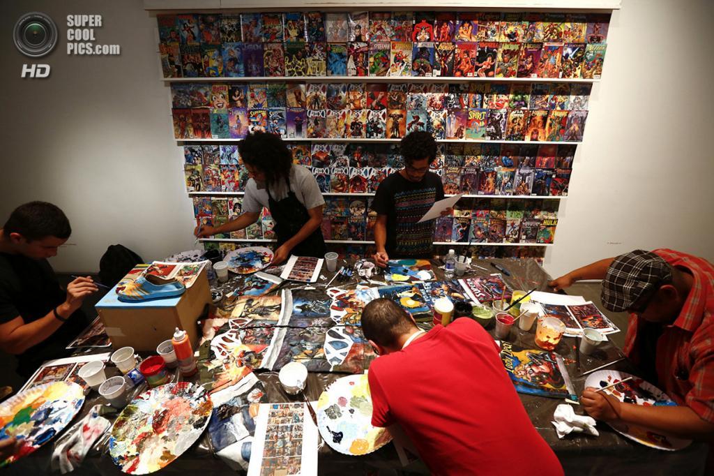 Венесуэла. Каракас. 1 ноября 2013 года. Художники срисовывают обложки комиксов на одежду Лю Болиня. (REUTERS/Jorge Silva)
