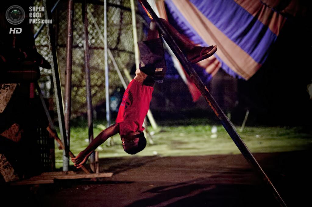 Бангладеш. Джамша. 31 октября. 11-летний Шариф Мосхрум свисает с балки за сценой. (Getty Images)