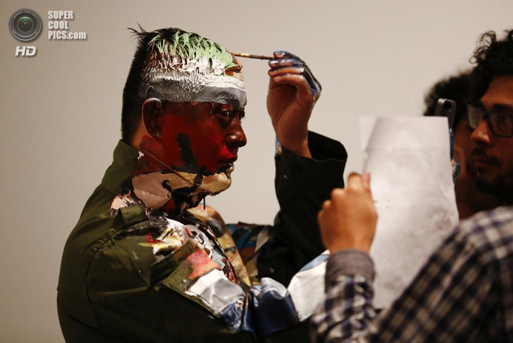 Венесуэла. Каракас. 2 ноября 2013 года. Лю Болинь разрисовывает сам себя, глядя на макет и зеркало. (REUTERS/Jorge Silva)