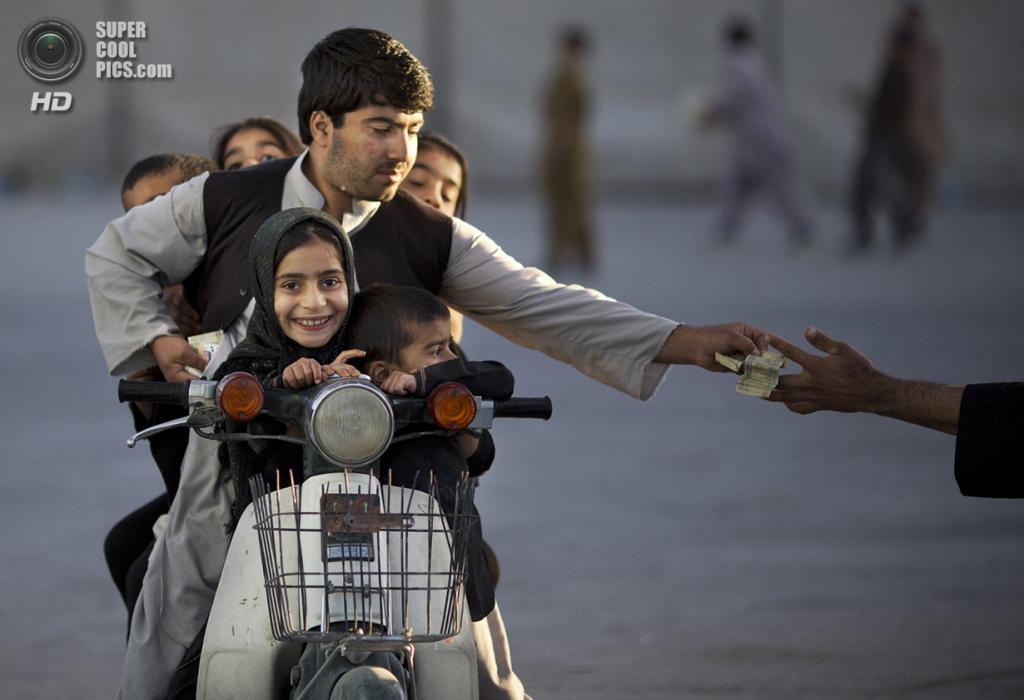 Афганистан. Кандагар. 1 ноября 2013 года. Афганец с пятью детьми на мотоцикле платит за въезд на территорию парка. (AP Photo/Anja Niedringhaus)