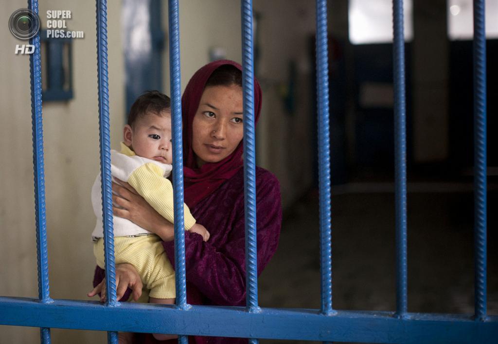 Афганистан. Кабул. 28 марта 2013 года. Афганская заключённая тюрьмы Бадам-Багх Нурия со своим новорожденным мальчиком. Она находится в тюрьме за то, что посмела подать на развод, получив вместо развода тюремный срок. Её возлюбленный, на котором она хотела жениться, так же был отправлен в тюрьму. (AP Photo/Anja Niedringhaus)