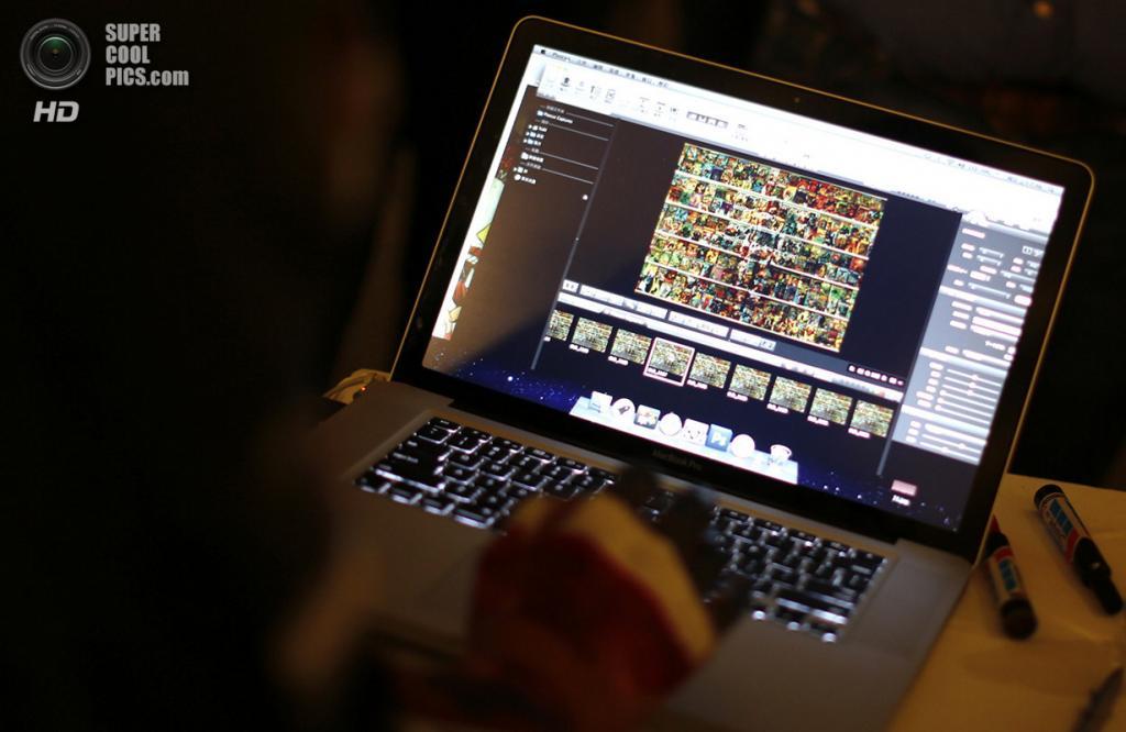 Венесуэла. Каракас. 2 ноября 2013 года. Лю Болинь оценивает результат перформанса на своём MacBook Pro. (REUTERS/Jorge Silva)