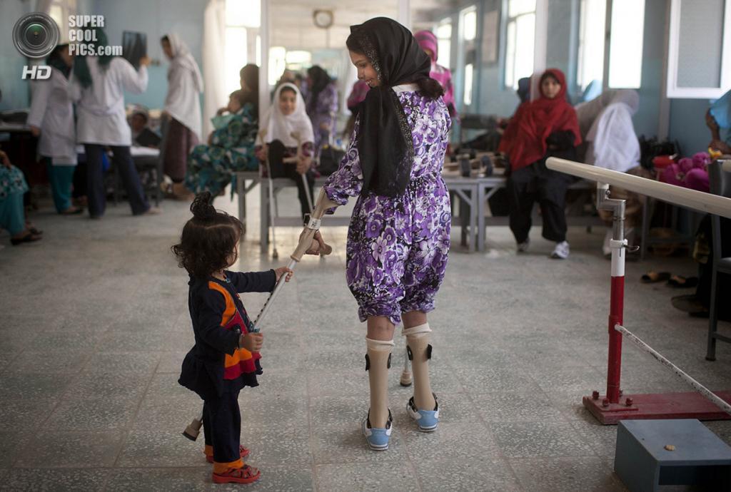 Афганистан. Кабул. 27 мая 2012 года. Девочка пытается ухватиться протезом за руку своей сестрёнки в реабилитационном центре ICRC, который с начала работы в 1988 году принял более 43 00 человек. (AP Photo/Anja Niedringhaus)