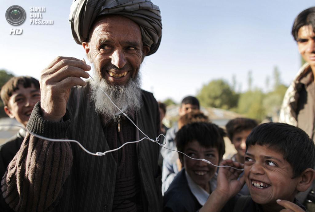 Афганистан. Фейзабад, Кундуз. 15 сентября 2009 года. Афганцы слушают музыку с iPod немецкого солдата. (AP Photo/Anja Niedringhaus)