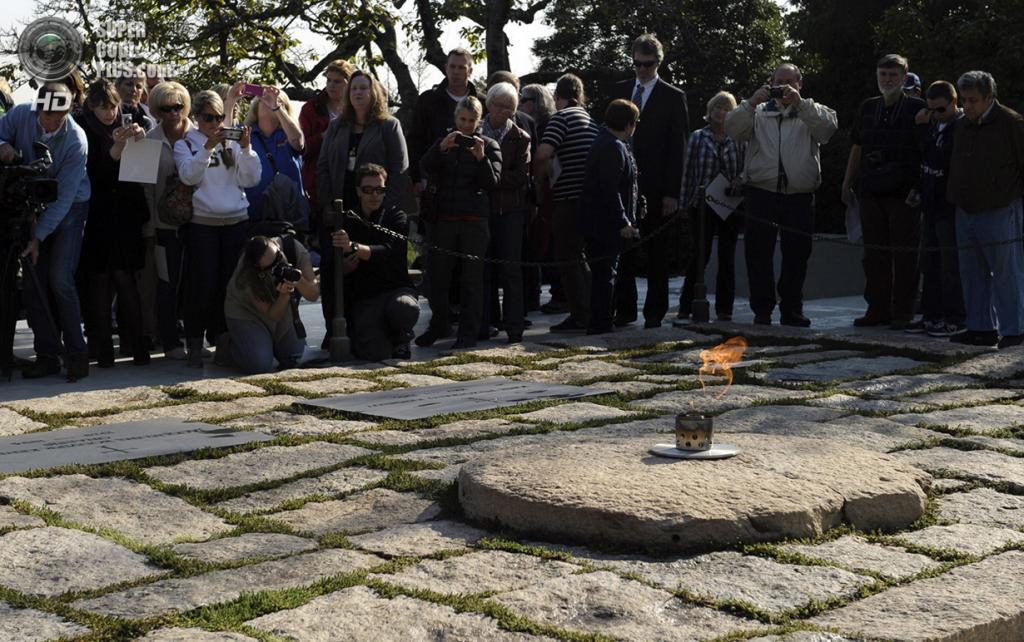 США. Арлингтон, Виргиния. 29 октября 2013 года. Люди у вечного огня на месте захоронения бывшего президента США Джона Ф. Кеннеди. (AP Photo/Susan Walsh)