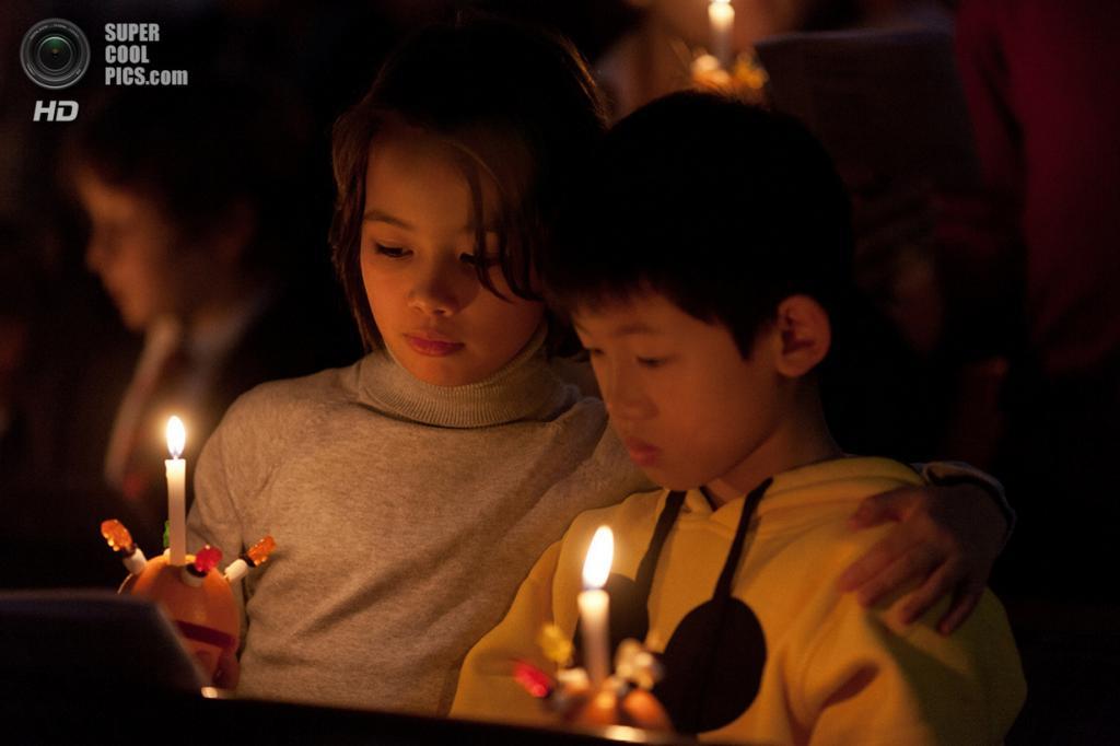 Китай. Гонконг. 24 декабря. Дети с кристинглами — «свечами Христа». Кристингл — это религиозный символ в форме апельсина, в который вставлена свеча; раздаётся детям на предрождественском богослужении. Свеча символизирует Иисуса Христа как «свет миру». Кристингл ввело в употребление Общество англиканской церкви по оказанию помощи детям, перенявшее его от немецкой Моравской церкви в 1960-х годах. (Anthony Wallace/AFP/Getty Images)