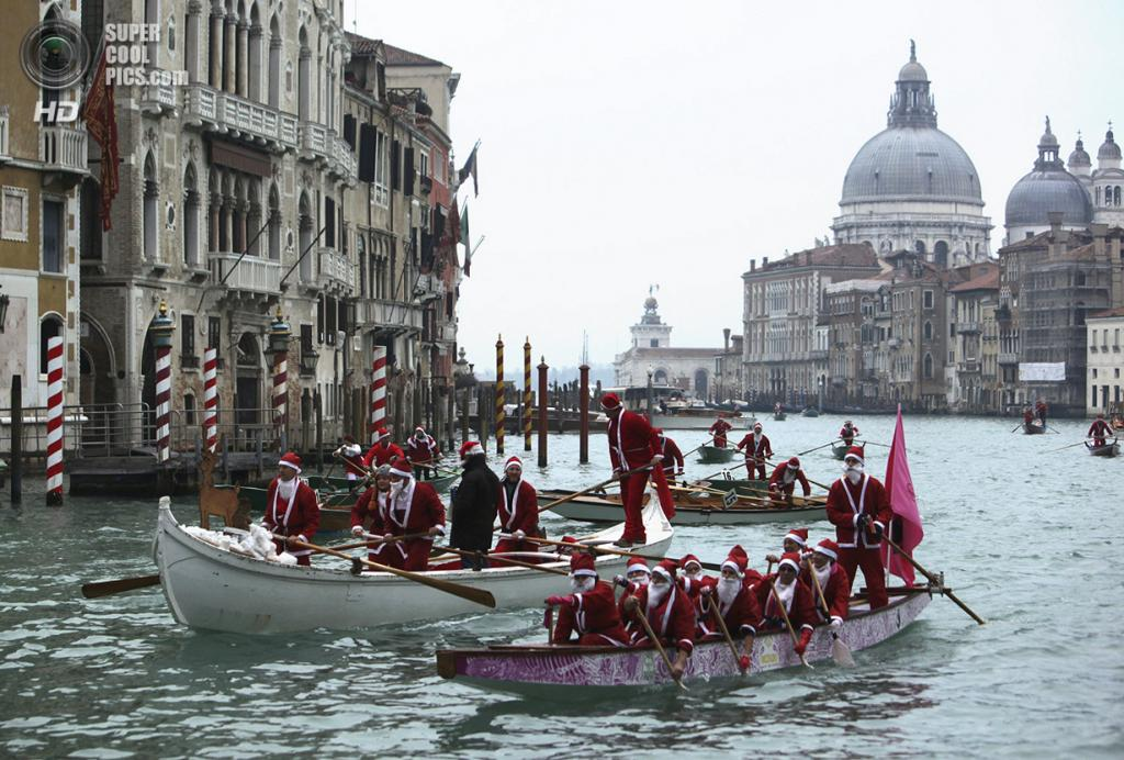 Италия. Венеция. 21 декабря. Традиционное соревнование по гребле в костюмах Санта-Клаусов. (REUTERS/Manuel Silvestri)