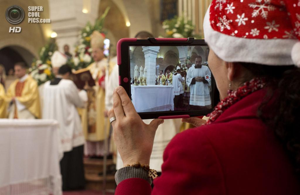 Палестина. Вифлеем. 25 декабря. Паломник снимает на iPad рождественскую мессу в Базилике Рождества Христова. (Oren Ziv/Getty Images)