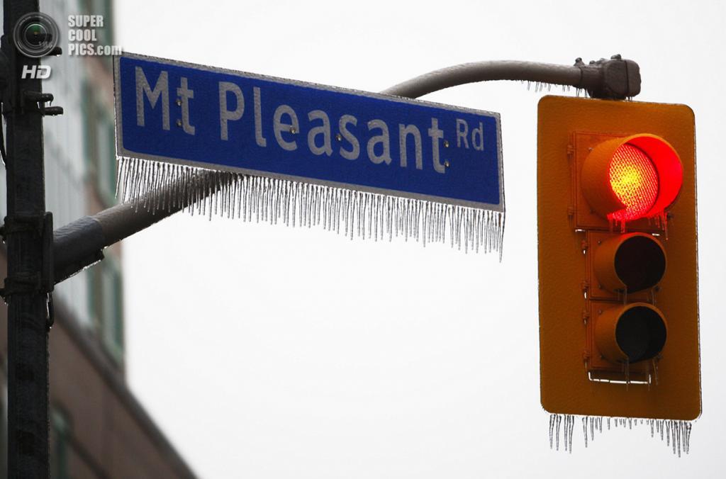 Канада. Торонто, Онтарио. 22 декабря. Сосульки на светофоре и дорожном знаке. (REUTERS/Hyungwon Kang)