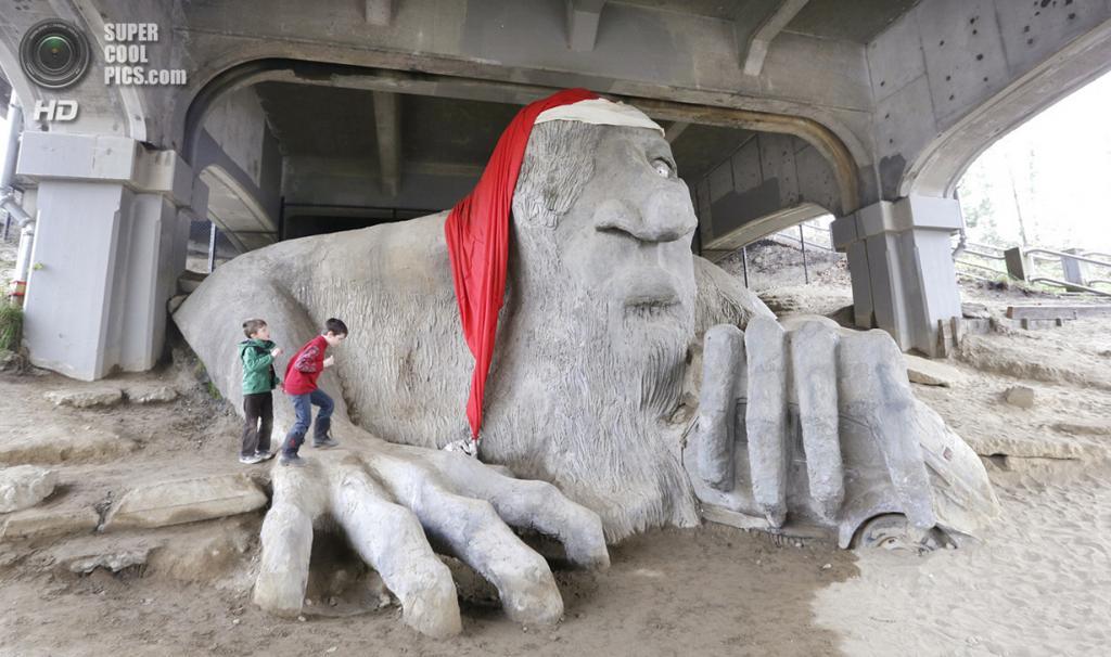 США. Сиэтл, Вашингтон. 24 декабря. Дети играют у «Фремонтского тролля» под мостом Аврора-бридж. (AP Photo/Elaine Thompson)