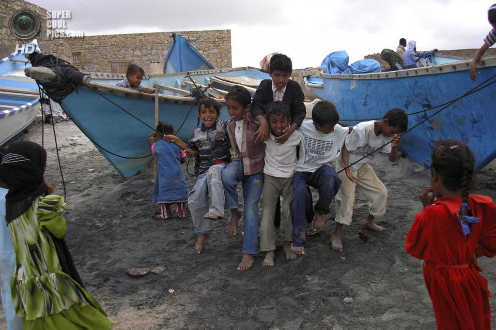 Дети играют среди рыбацких лодок. (REUTERS/Alistair Lyon)