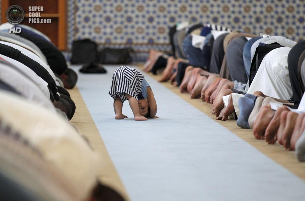 Франция. Страсбург, Нижний Рейн, Эльзас. 9 июля. Ребёнок из мусульманской семьи «молится» вместе со взрослыми на полуденной молитве в Большой мечети во время священного месяца Рамадан. (REUTERS/Vincent Kessler) — Пост на сайте