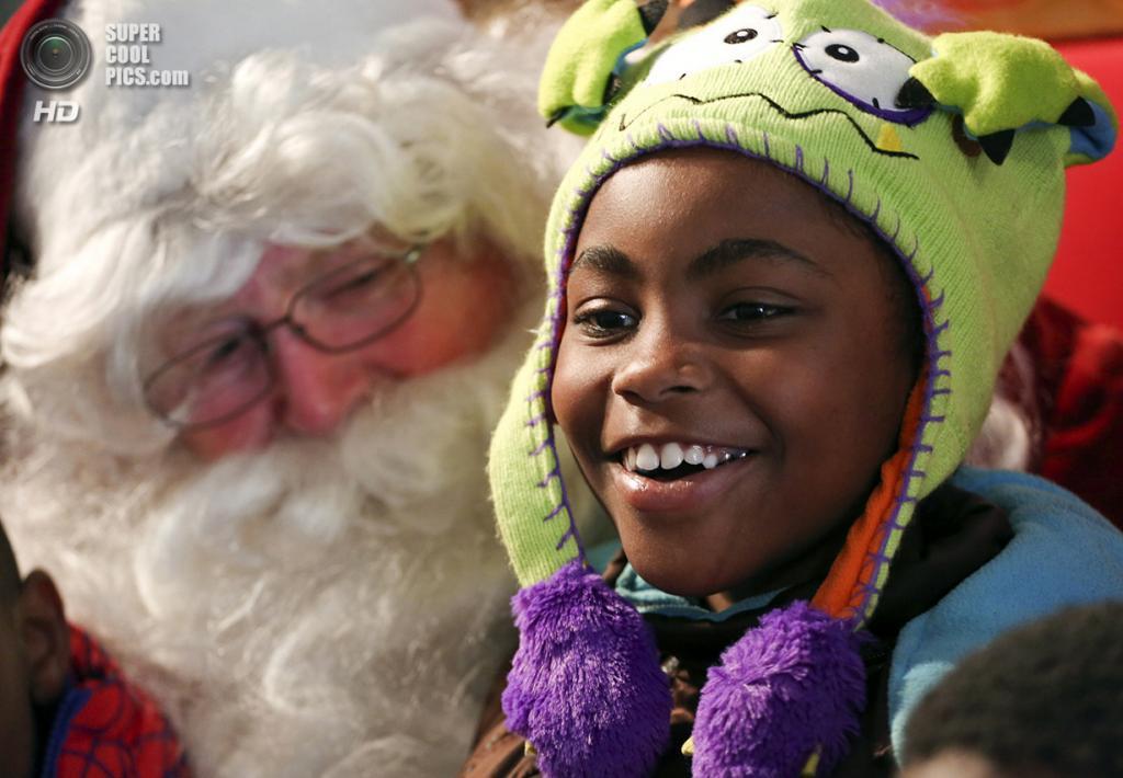 США. Лос-Анджелес, Калифорния. 24 декабря. 8-летняя Фейт Каллион улыбается на коленях Санта-Клауса во время Сочельника, устроенного для бездомных и малоимущих благотворительной организацией Los Angeles Mission. (REUTERS/Jonathan Alcorn)