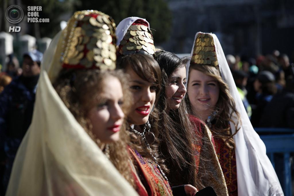 Палестина. Вифлеем. 24 декабря. Девушки в традиционных палестинских костюмах участвуют в рождественской процессии перед Базиликой Рождества Христова. (REUTERS/Darren Whiteside)