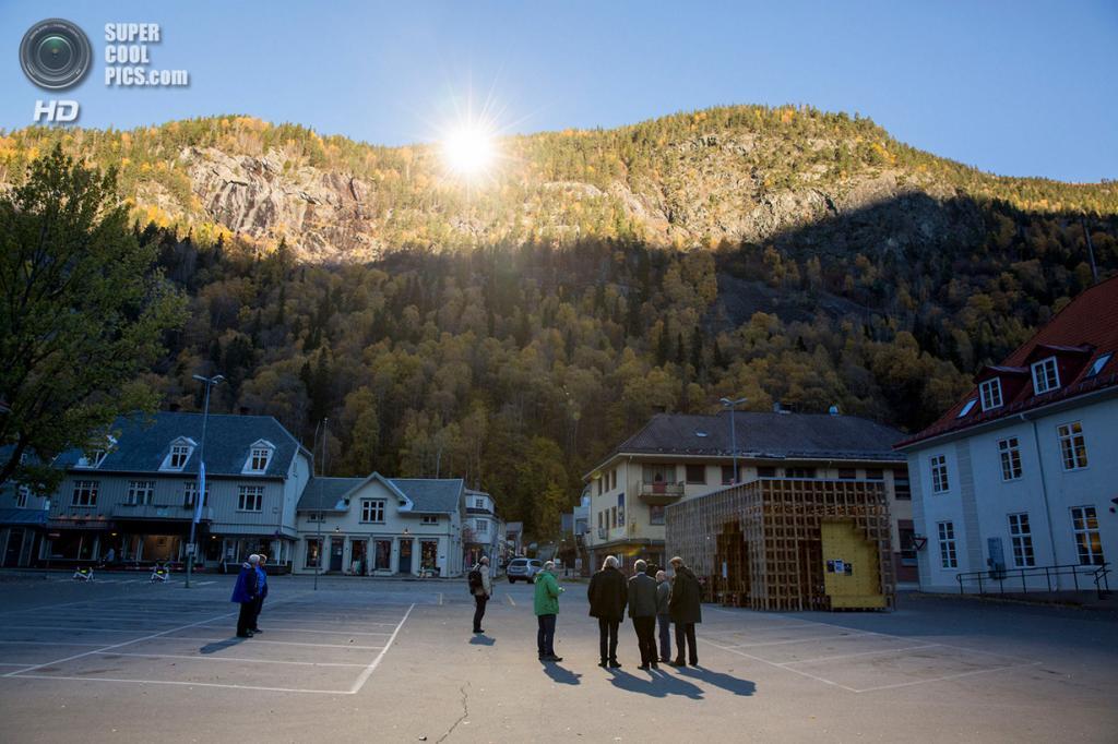 Норвегия. Рьюкан, Телемарк. 18 октября. Местные жители и туристы собираются перед ратушей, чтобы полюбоваться отражением солнца в гигантских зеркалах, установленных над долиной. Более пяти месяцев в году Рьюкан был отрезан от солнца горами, однако теперь 600 м² солнечного света будут доставлять прямиком на центральную площадь гигантские зеркала. (REUTERS/Tore Meek/NTB Scanpix) — Пост на сайте