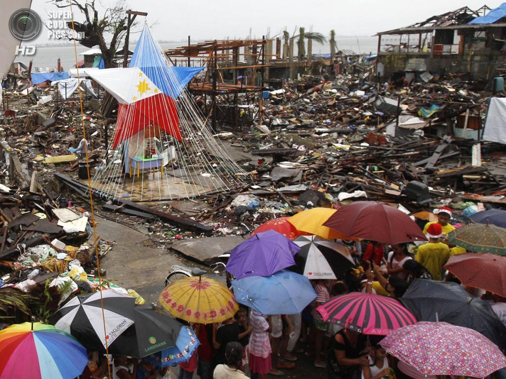 Филиппины. Таклобан, Лейте. 25 декабря. Дети выстроились в очередь за подарками рядом с алтарём, украшенным филиппинским национальным флагом. В этом году Рождество и Новый Год на Филиппинах омрачены разрухой после тайфуна «Хайян». (AP Photo/Achmad Ibrahim)