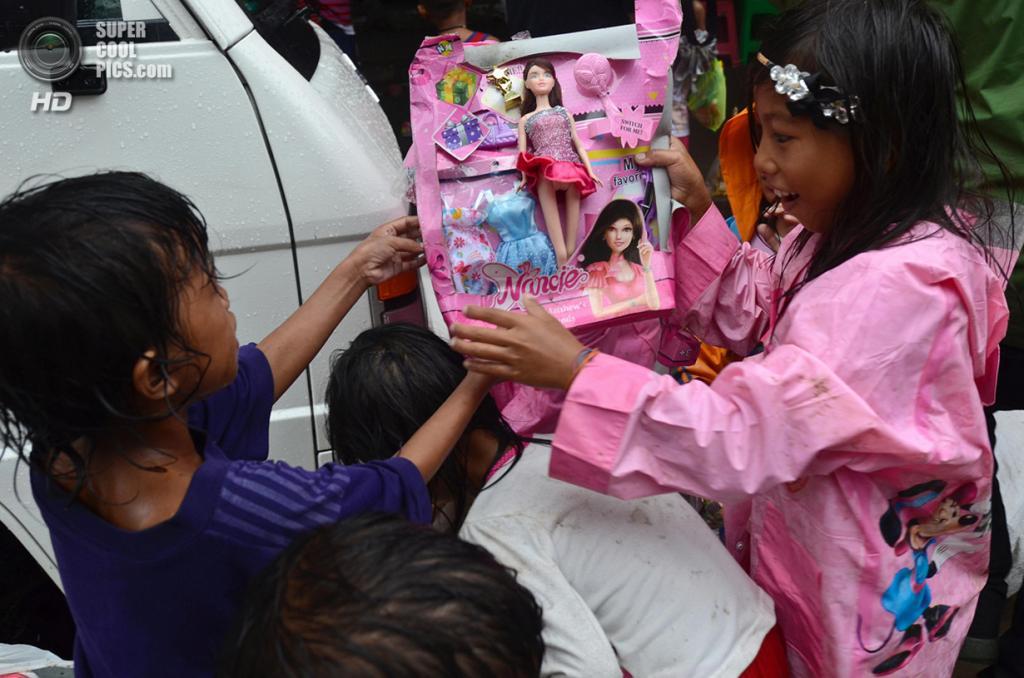 Филиппины. Таклобан, Лейте. 25 декабря. Девочка демонстрирует свой подарок на Рождество — куклу Nancie, найденную среди руин магазина. (Dondi Tawatao/Getty Images)