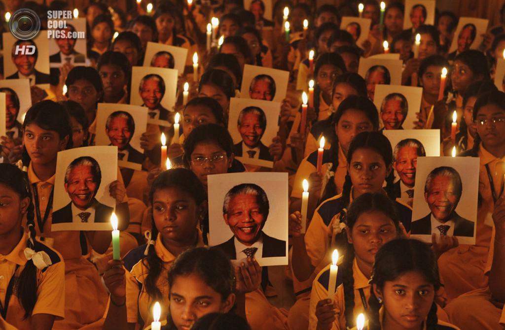 ЮАР. Йоханнесбург. 6 декабря 2013 года. Скорбящие держат портреты Нельсона Манделы. (Reuters/Babu)