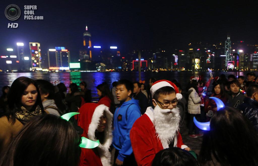Китай. Гонконг. 24 декабря. Праздные люди у гавани Виктория. (AP Photo/Kin Cheung)