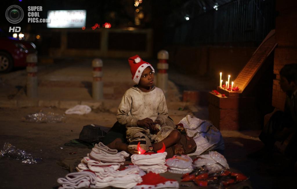 Индия. Нью-Дели. 24 декабря. Мальчик продает рождественские сувениры у Собора Святейшего Сердца Иисуса. (AP Photo/Altaf Qadri)