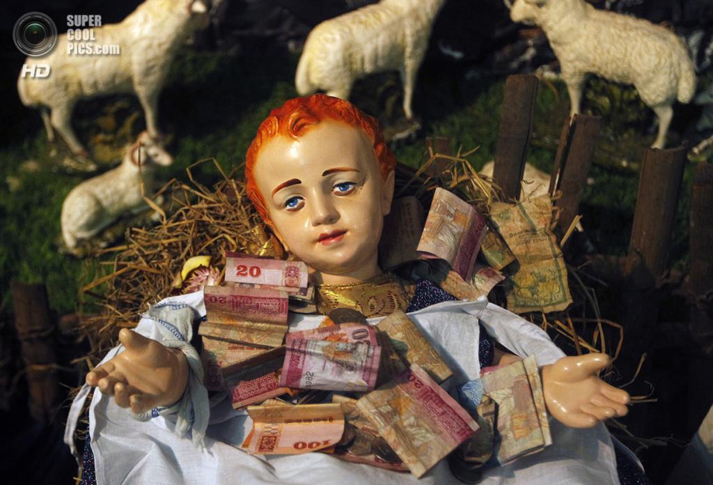 Шри-Ланка. Коломбо. 25 декабря. Пожертвования, оставленные верующими у фигурки младенца Иисуса во время рождественской мессы. (REUTERS/Dinuka Liyanawatte)