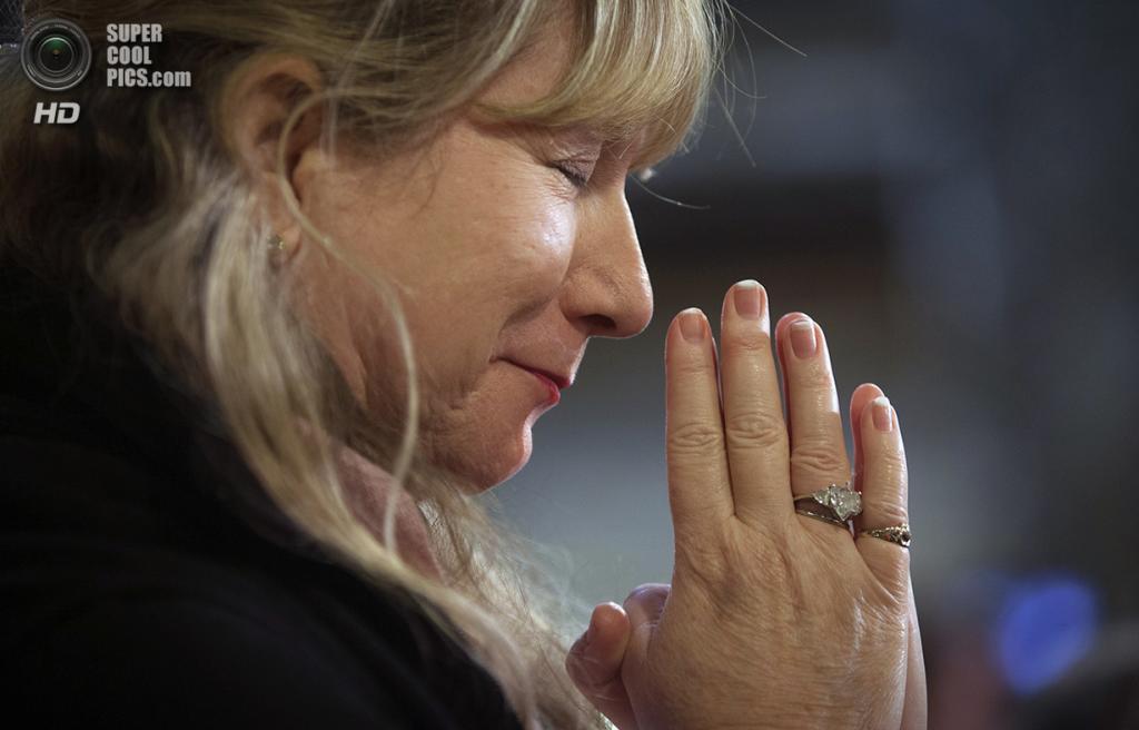 США. Нью-Йорк. 25 декабря. Женщина склонила голову в молитве во время всенощной в Соборе Святого Патрика. (REUTERS/Carlo Allegri)