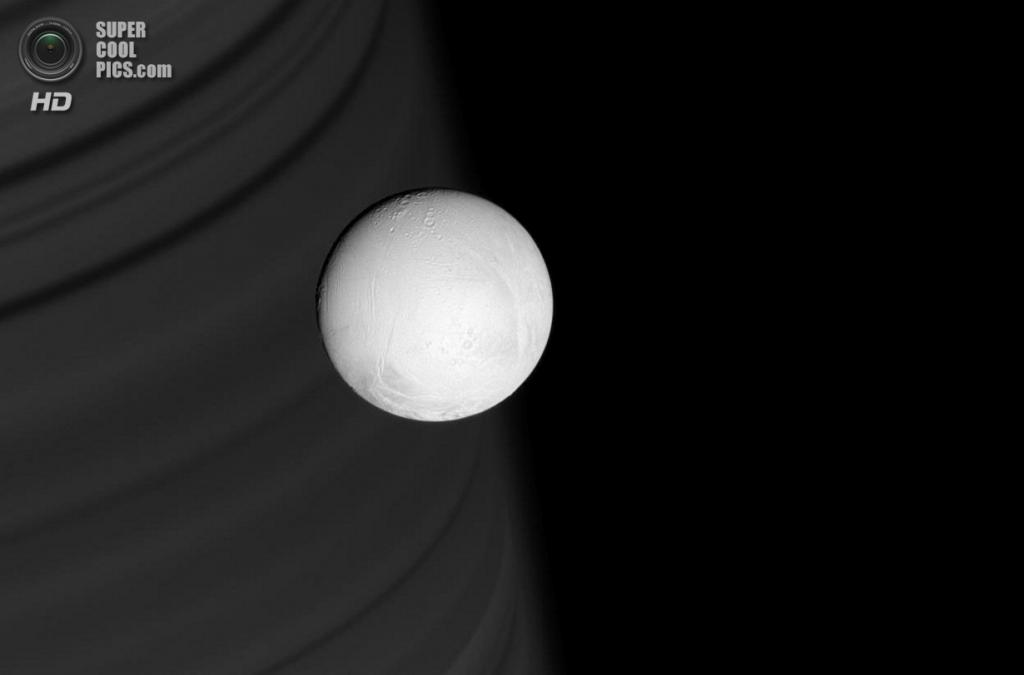 Кольца, оттеняя поверхность далёкого Сатурна, создают изысканный фон для блестящей белой сферы Энцелада. (NASA/JPL-Caltech/SSI)