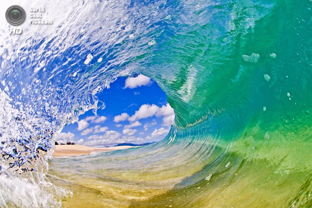 «Хрустальный шар». Лёгкий дневной ветер сохранил поверхность воды хрустально-чистой, подчёркивая песок на морском дне и облака на небе, видимые сквозь волну. (Clark Little)