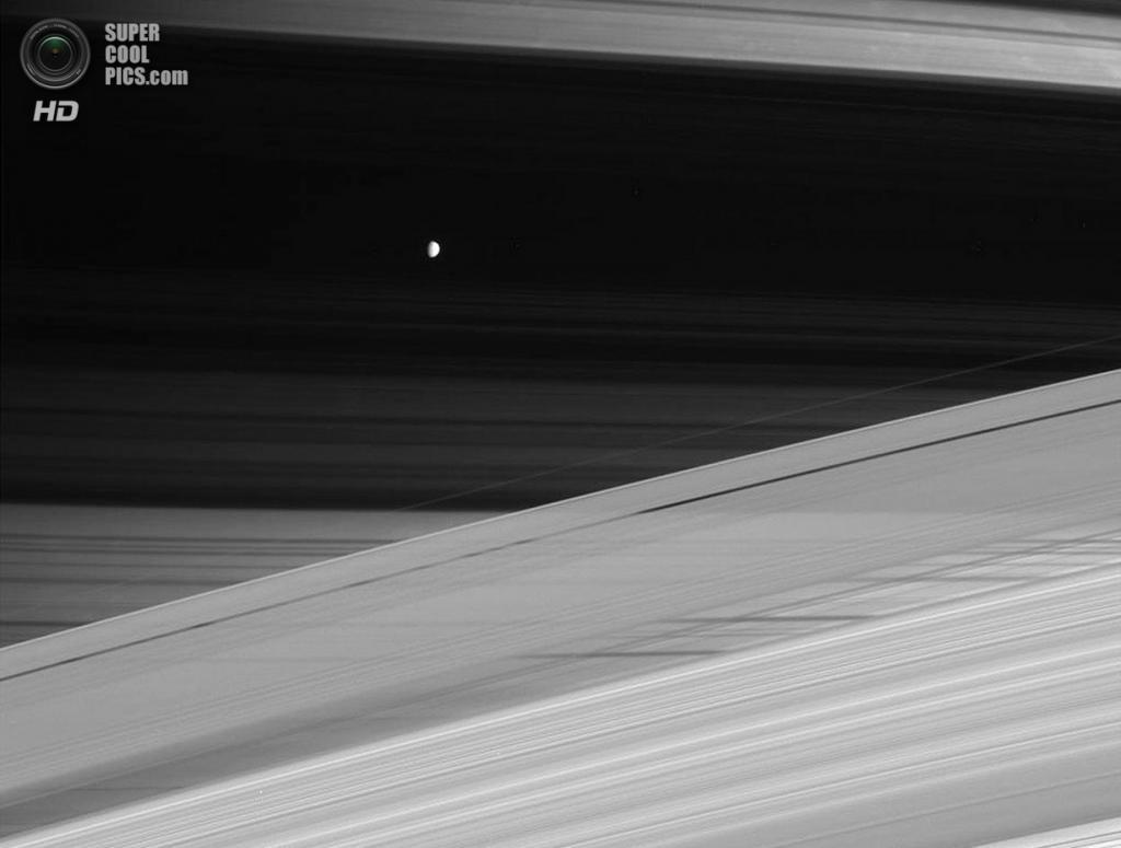 Лабиринт Сатурна и его колец на фоне ледяного спутника Мимаса. Кольца отбрасывают тёмные тени на северном полушарии газового гиганта, создавая эффект фотонегатива. (NASA/JPL-Caltech/SSI)