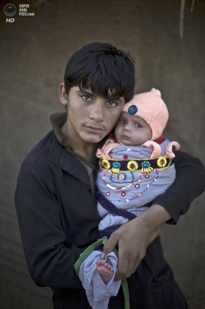 Шахзада Салим, 15 лет, со своим племянником Сатарой, 2 месяца. (AP Photo/Muhammed Muheisen)