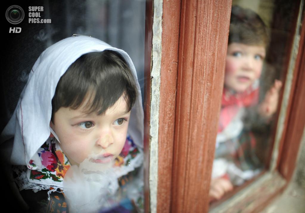 Македония. Вевчани, Юго-Западный регион. 13 января 2009 года. Дети наблюдают за карнавальным шествием. (REUTERS/Ognen Teofilovski)
