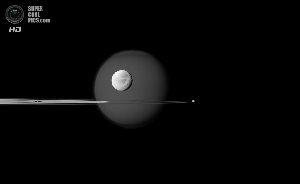 Сразу четыре спутника Сатурна в одном кадре: огромный Титан на заднем плане, чуть меньшая Диона, еще меньшая Пандора (справа от колец) и совсем крошечный Пан, который спрятался в щели Энке — тёмном промежутке в ярком кольце А. (NASA/JPL-Caltech/SSI)
