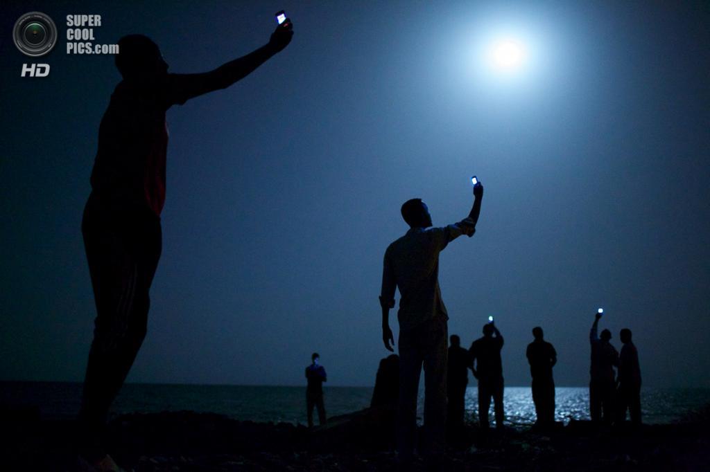 Гран-при конкурса: Джибути. 26 февраля 2013 года. Африканские мигранты под покровом ночи пытаются поймать более дешёвый сигнал из соседнего Сомали, чтобы отослать сообщение близким. (AP Photo/John Stanmeyer, VII for National Geographic)