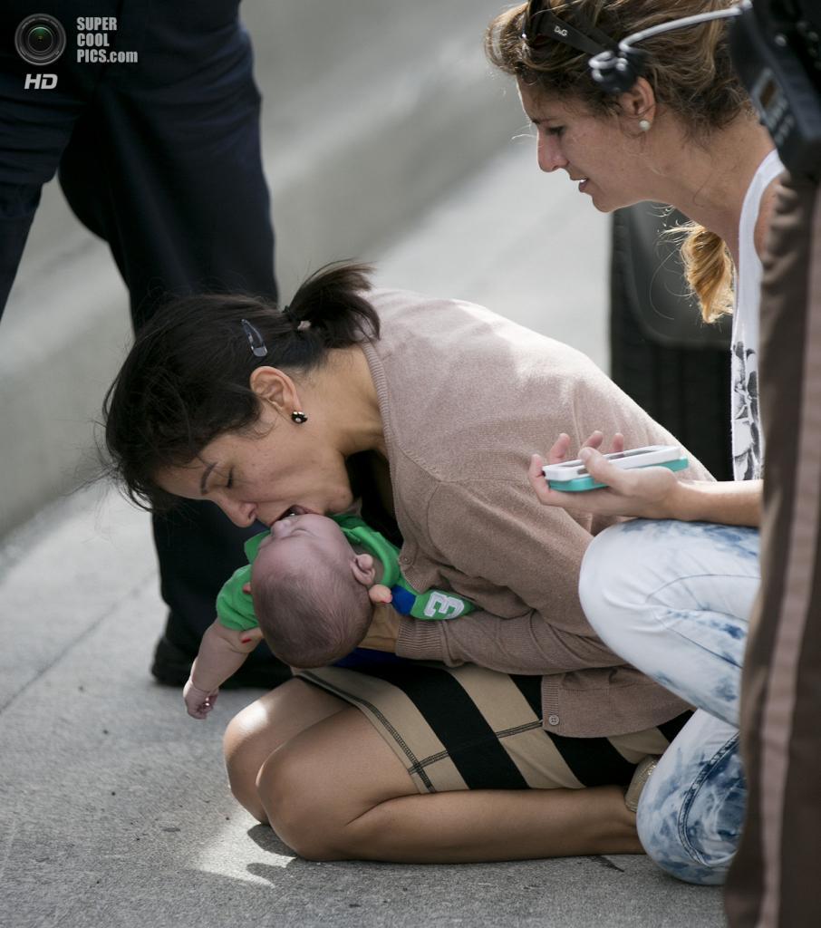 США. Свитуотер, Флорида. 20 февраля. Памела Раусео делает искусственное дыхание своему 5-месячному племяннику Себастьяну. Справа — Лусилья Годой, остановившая свой автомобиль, чтобы помочь в спасении. (AP Photo/Al Díaz, Miami Herald)