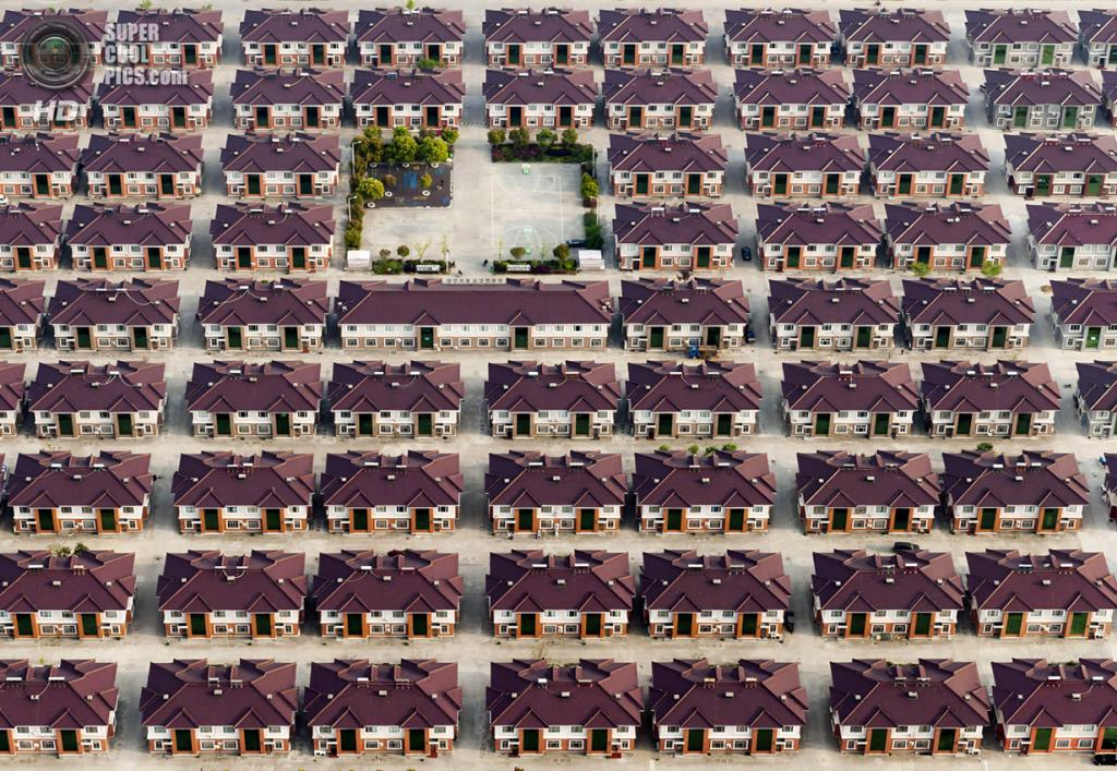 Массив одинаковых домов с детской и баскетбольной площадками посредине. Место съёмки: Китай. Цзянинь, Цзянсу. (Kacper Kowalski/2014 Sony World Photography Awards)