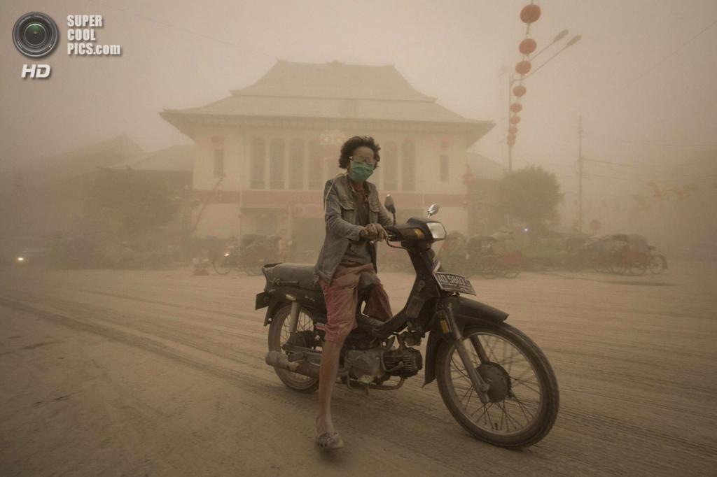 Индонезия. Суракарта, Центральная Ява. 14 февраля. Женщина на мотоцикле в вулканическом пепле после извержения Келуда. (AP Photo/Hafidz Novalsyah)