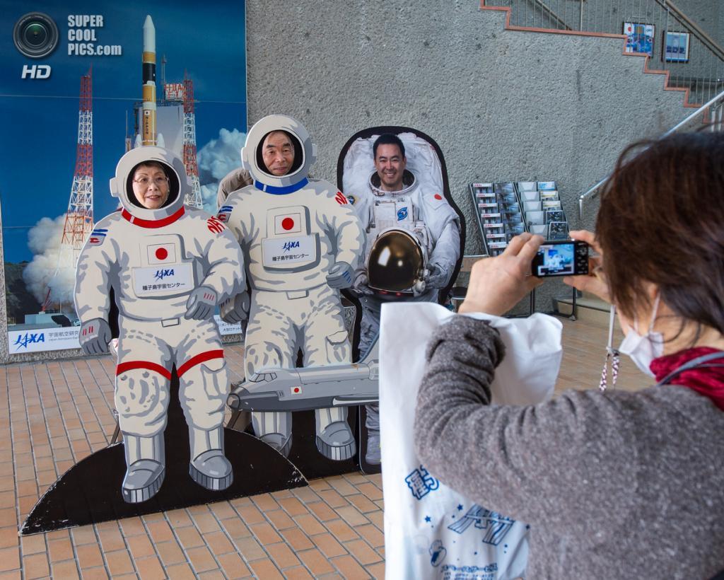 Япония. Танегасима, Кагосима. 23 февраля. Туристы фотографируются у тантамарески в виде космонавтов на территории Космического центра Танэгасима. (NASA/Bill Ingalls)