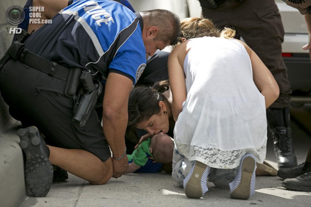 США. Свитуотер, Флорида. 20 февраля. Памела Раусео делает искусственное дыхание Себастьяну. К женщинам пришёл на помощь полицейский Амаурис Бастидас. (AP Photo/Al Díaz, Miami Herald)