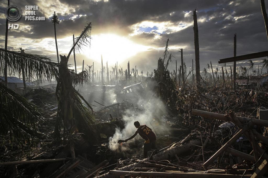 Мужчина тушит пламя среди руин после тайфуна «Хайян». Место съёмки: Филиппины. Танауан, Батангас. (Dan Kitwood/2014 Sony World Photography Awards)