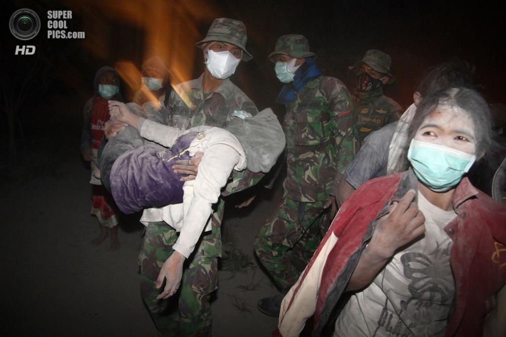 Индонезия. Маланг, Восточная Ява. 14 февраля. Индонезийские солдаты помогают эвакуировать пострадавших после извержения Келуда. (Aman Rochman/AFP/Getty Images)