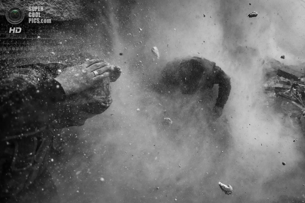 Spot News Stories, 1-ое место: Сирия. Дамаск. 30 января 2013 года. Сирийские мятежники прячутся в укрытии среди летящего мусора и шрапнели во время танкового огня сирийских солдат. (AP Photo/Goran Tomasevic, Reuters)
