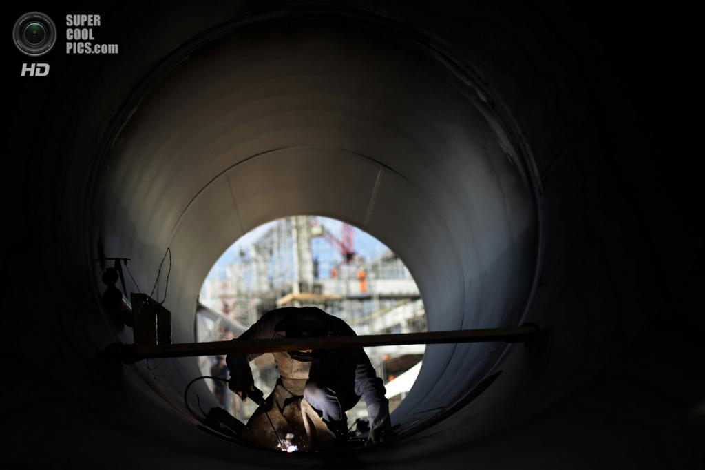 Бразилия. Кабробо, Пернамбуку. 24 января. Рабочий приваривает трубу на насосной станции. (REUTERS/Ueslei Marcelino)