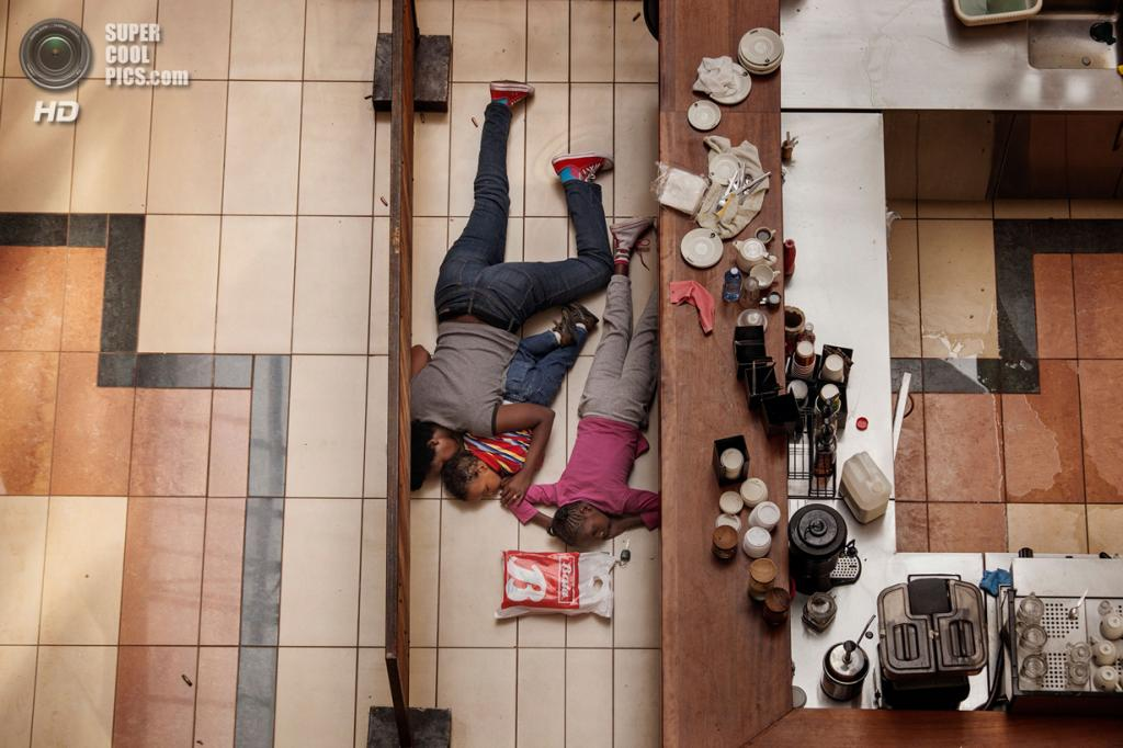 Spot News Stories, 2-ое место: Кения. Найроби. 21 сентября 2013 года. Женщина с детьми прячется за полками во время теракта в торговом центре «Уэстгейт». (AP Photo/Tyler Hicks, The New York Times)