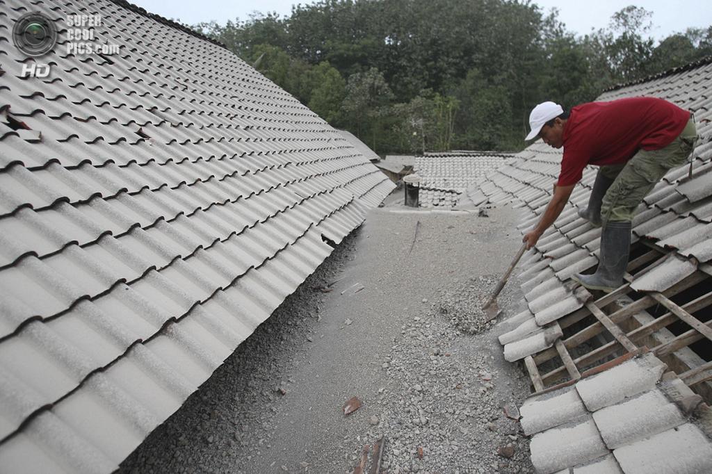 Индонезия. Блитар, Восточная Ява. 14 февраля. Мужчина чистит крышу от вулканического пепла. (AP Photo/Trisnadi)